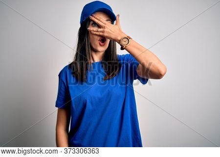 Young delivery woman with blue eyes wearing cap standing over blue background peeking in shock covering face and eyes with hand, looking through fingers with embarrassed expression.
