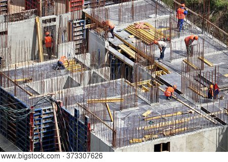 Workers Laying Concrete Floors And Building Walls On Construction Site. House Development, Residenti