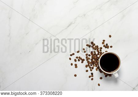 Cup With Coffee And Coffee Grains On A Marble Table. Concept Breakfast, Black Coffee, Coffee For The