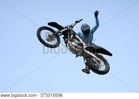 Rider In A Helmet On A Black Motorcycle Jumps Against The Sky