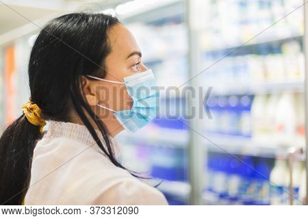 Woman Buying Food In Supermarket. She Is Wearing Protective Mask And Looking At The Dairy Section Of