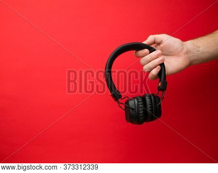 A Young Woman Holds A Pair Of Black Wireless Headphones In Her Hand. Hand Of A Girl With Headphones