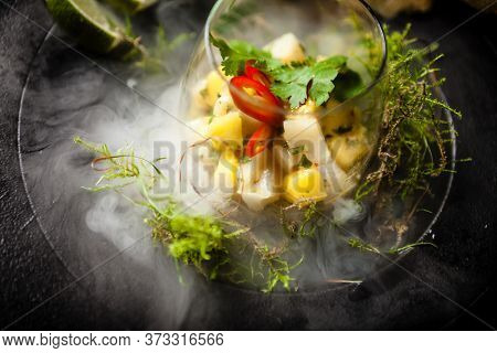 Scallop ceviche with mango, chilli and cilantro served with liquid ice smoke in a plate. Delicious healthy food closeup served for lunch on a table in modern gourmet cuisine restaurant.