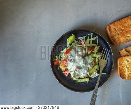 Coleslaw With Vegetables, Tomatoes And Cucumbers With Sauce In A Black Ceramic Plate And Toasted Toa