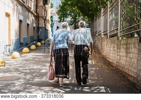 Senior Couple Walking Arm In Arm Along The Street. Back View. Concept Of Supporting Each Other In Ol