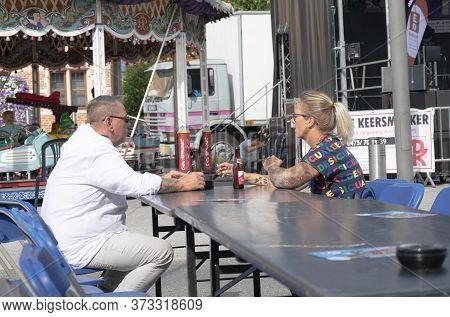Sint Gillis Waas, Belgium, August 3, 2019 Couple Enjoying A Bottle Of Beer In The Sun On A Terrace D
