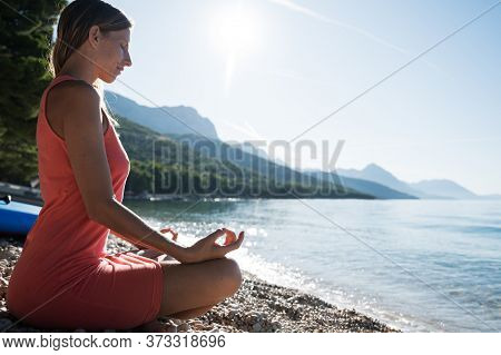 Profile View Of A Young Woman Sitting On Pebble Beach In Lotus Position, Meditating By The Calm Morn