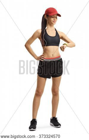 Full length portrait of a young sporty female runner looking at armband isolated on white background