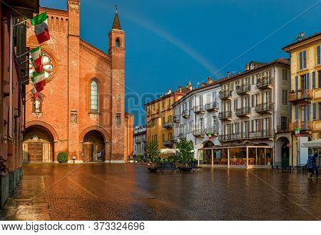 Wet cobblestone town square, old houses and San Lorenzo cathedral lit by sunlight under rainy sky with rainbow in Alba, Piedmont, Northern Italy.