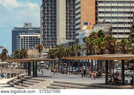 TEL AVIV, ISRAEL - JULY 19, 2017: People walking on promenade along modern hotel buildings in Tel Aviv - city on Mediterranean coastline, economic and technological center of Israel.