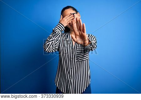 Beautiful blonde woman with blue eyes wearing striped shirt and glasses over blue background covering eyes with hands and doing stop gesture with sad and fear expression. Embarrassed and negative.