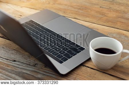 Laptop With Cup Coffee On Wooden Table In Home Office