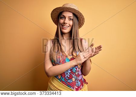 Young beautiful blonde woman wearing swimsuit and summer hat over yellow background clapping and applauding happy and joyful, smiling proud hands together