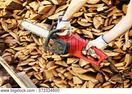 Man Sawing Wood With Electric Saw.  Close-up - Of Woodcutter Sawing Chain Saw In Motion.