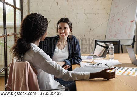 Two attractive smiling smart multiethnic women entrepreneurs working over new project in a modern office, sitting at the desk