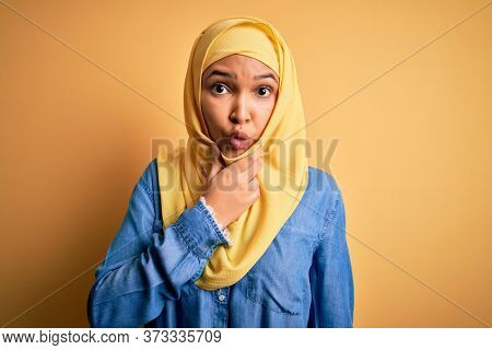 Young beautiful woman with curly hair wearing arab traditional hijab over yellow background Looking fascinated with disbelief, surprise and amazed expression with hands on chin
