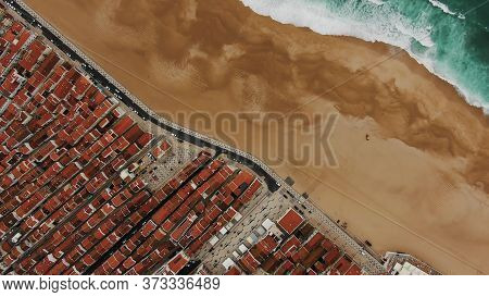 Pictorial Drone View Of Emerald Ocean Washing Empty Amber Sand Beach Near Tourist Town With Brown Ho