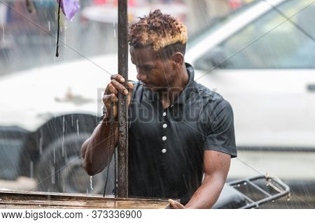 Nosy Be, Madagascar - January 17th, 2019: A Man Working Taking Apart His Street Stall Under A Heavy