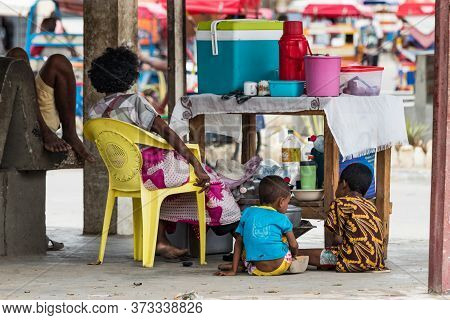 Toliara, Madagascar - January 10th, 2019: A Malagasy Mother With Her Kids Selling Tea And Coffee Wit