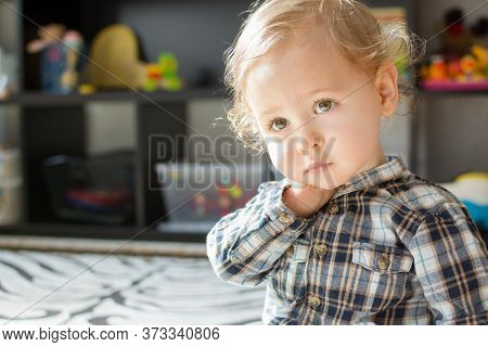Sweet Little Baby Boy Portrait At Home, With Toys In The Background