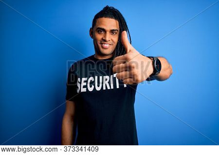 Young african american afro safeguard man with dreadlocks wearing security uniform happy with big smile doing ok sign, thumb up with fingers, excellent sign
