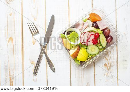 Vegetables Salad In Plastic Bowl On White Wood Table