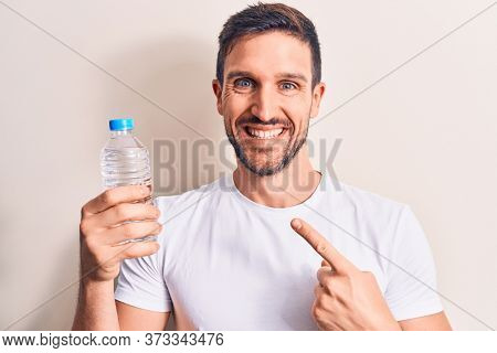 Young handsome man drinking bottle of water to refreshment over isolated white background smiling happy pointing with hand and finger