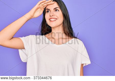 Young beautiful brunette woman wearing casual white t-shirt over purple background very happy and smiling looking far away with hand over head. Searching concept.