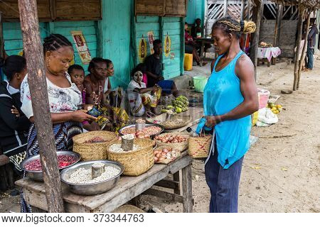 Andavadoaka, Madagascar - January 13th, 2019: Local Malagasy Seller Selling Beans And Food Standing