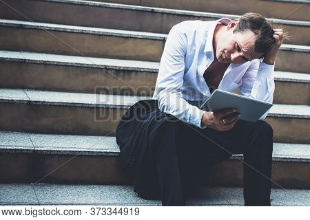 Caucasian, Businessmen Sitting On Conreete Stairs, Looking Tablets And Being Stressed Because Of Bus