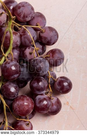 Close Up Branch Of Dark Red Grape On Pink Concrete Background. Top View, Flat Lay, Concept Of Sweet