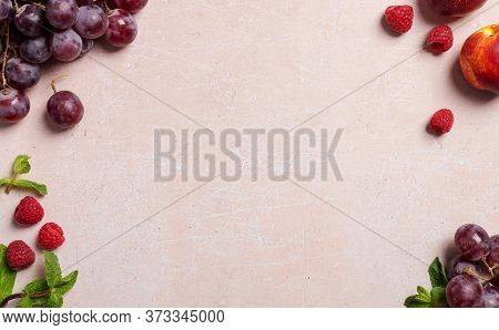 Frame With Different Fruits At Borders At Pink Concrete Background. Copy Space With Grape, Nectarine
