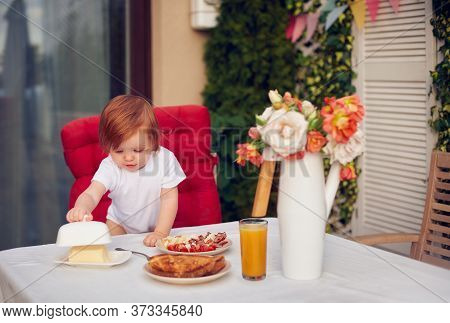 Curious Redhead Baby Girl Exploring Dishes On Breakfast Table At The Patio