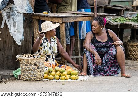 Toliara, Madagascar - January 10th, 2019: Two Malagasy Women Street Vendors Discussing Sitting On Th