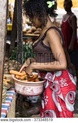 Toliara, Madagascar - January 10th, 2019: Young Malagasy Woman Putting Carrots On A Plastic Basin At