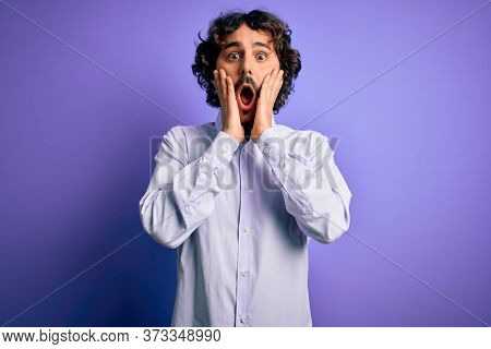 Young handsome business man with beard wearing shirt standing over purple background afraid and shocked, surprise and amazed expression with hands on face