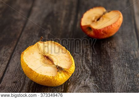 Wilted Rotten Half Apples On A Wooden Surface Background