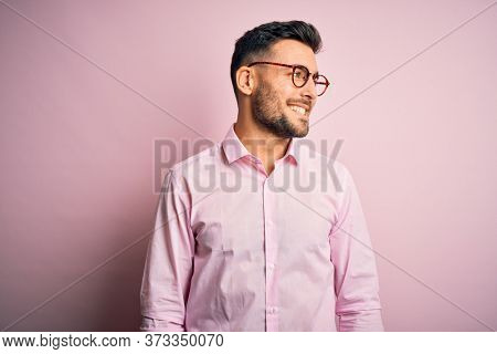 Young handsome man wearing elegant shirt and glasses standing over pink background looking away to side with smile on face, natural expression. Laughing confident.