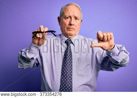 Senior grey haired man holding correction glasses over purple background with angry face, negative sign showing dislike with thumbs down, rejection concept