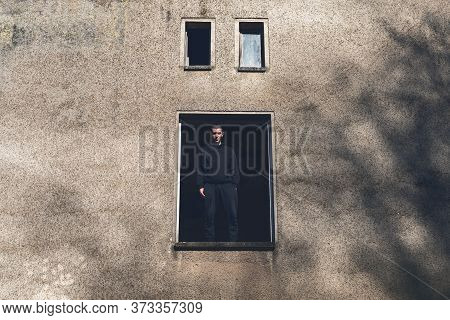 Smiling Young Man Stands In An Open Window Of A House