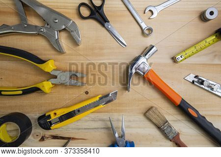 A High Angle Shot Of Many Working Instruments On A Light Wooden Surface. Construction Tools On Woode