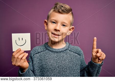 Young little caucasian kid showing smiley face on a paper note as happy message surprised with an idea or question pointing finger with happy face, number one