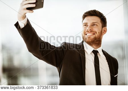 Business concept. Happy smiling young businessman at the office standing and making selfie or video chat conference using cell phone at work. Man in suit indoors on glass window background.