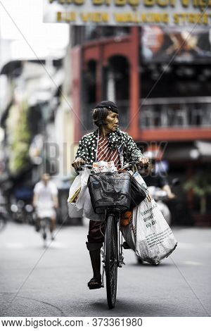 Ho Chi Minh (saigon) / Vietnam - 9.06.2020. Vietnamese Woman Is Going Down The Street By Bicycle.