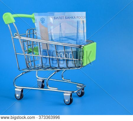 Russian Rubles In A Trolley On A Blue Background. Grocery Basket And 2000 Ruble Bills. Russian Curre