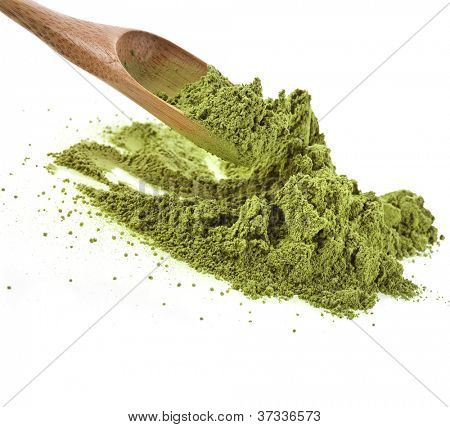 pile of powdered green tea with bamboo tea spoon , isolated on white background