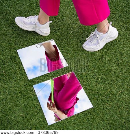 A Girl In Pink Trousers And White Sneakers Walks Past The Mirror. Reflection In A Mirror With An Unu