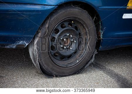 Kyiv, Ukraine - June 21, 2020: Wheel Of A Car With An Old Tire. Obsolete, Damaged Tire. Torn And Ful