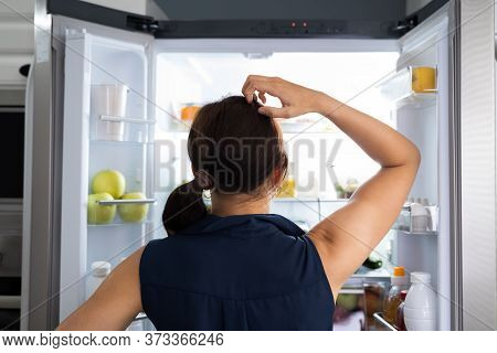 Hungry Women Looking At Food Inside Fridge