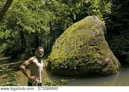 Man Visiting An Ancient Sacred Place With Glacial Hera Giant Erratic Stone